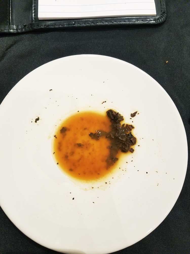 Dregs of tea and some tea leaves in the bottom of the saucer