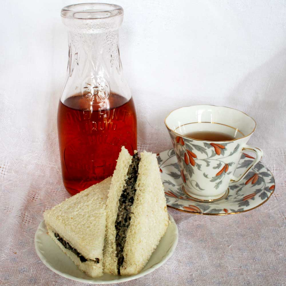 Image of crustless sandwich on a plate with pitcher and cup of tea