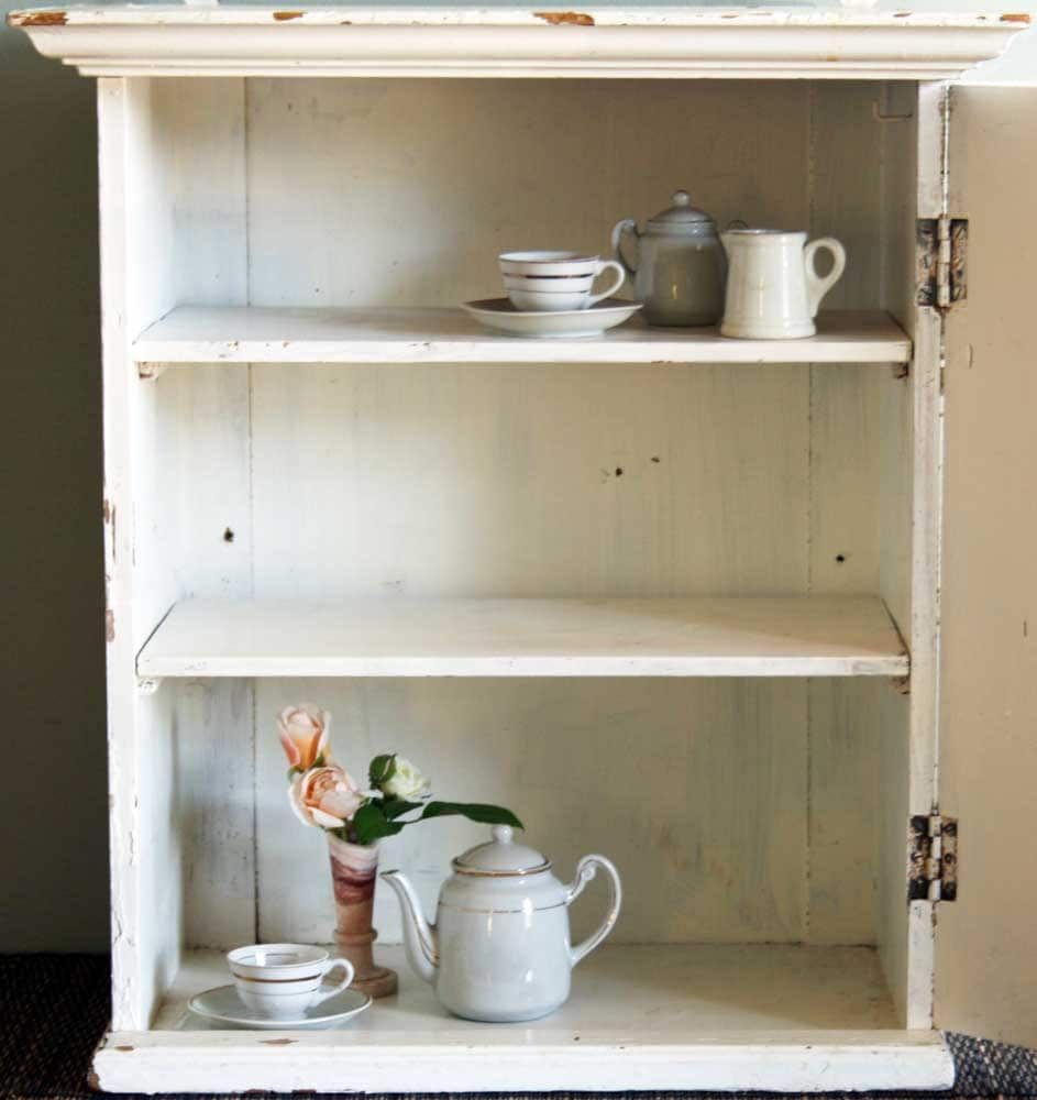 Image of open cupboard containing some tea dishes and a vase with flowers