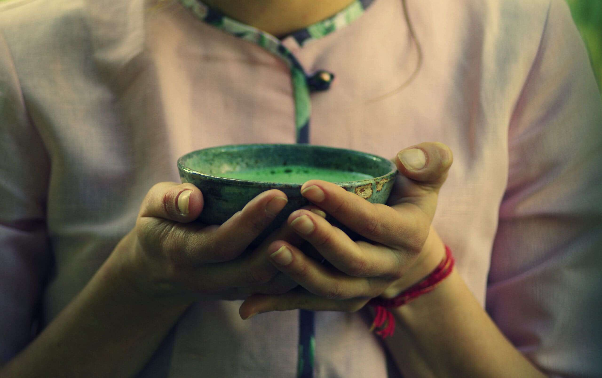 Person holding a bowl of frothy matcha tea, with a deep umami sensory experience