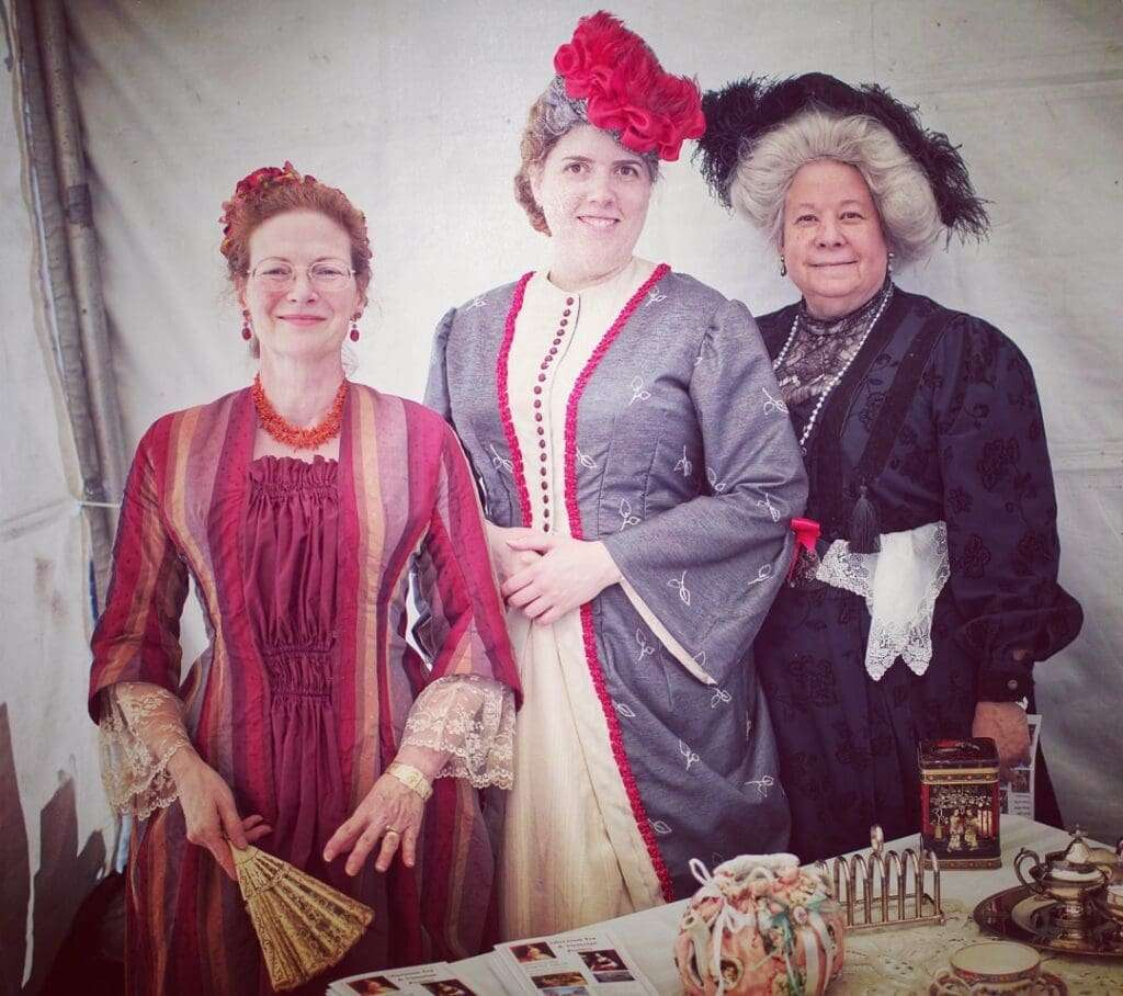 Image of ladies in Victorian attire with teapots on table in front of them