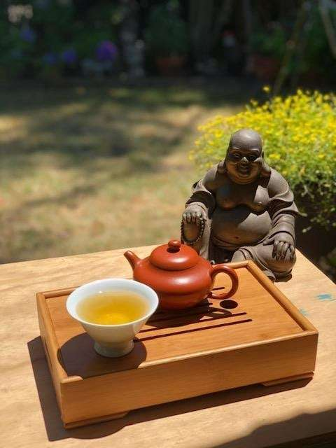 A photo of a tea cup of tea and teapot on a Chinese tea tray in front of a statuette of the Buddha, with grass in the background