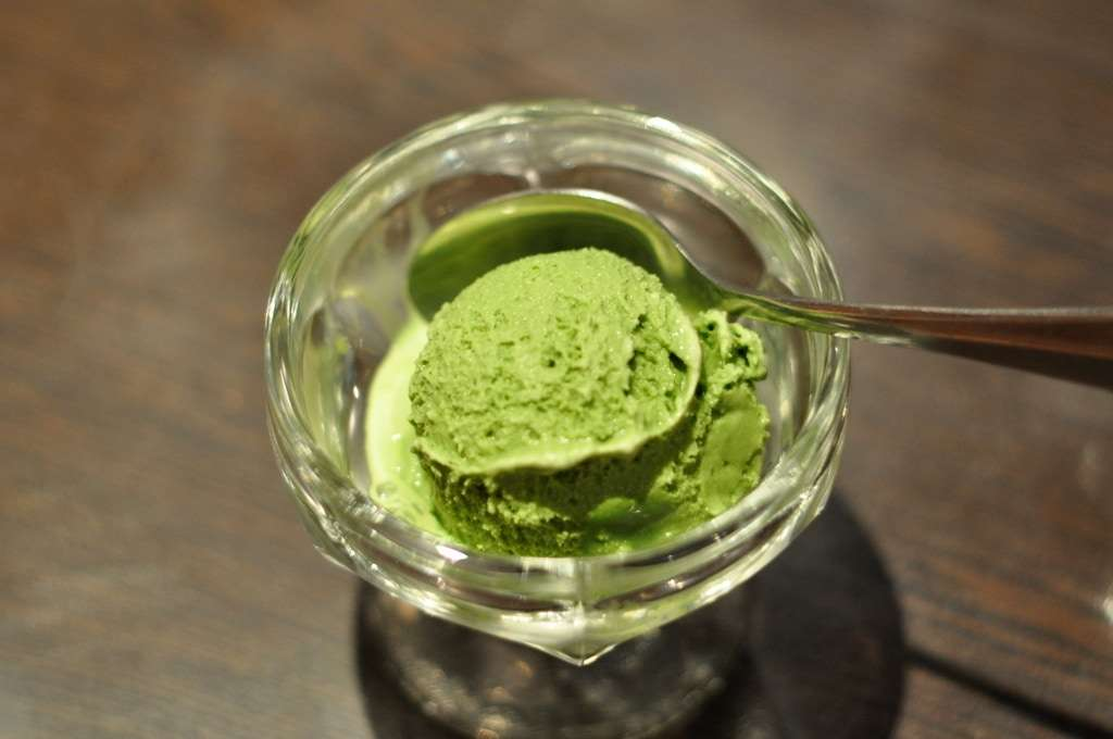 Photo of a glass dish with a spoon and a scoop of delicious matcha ice cream