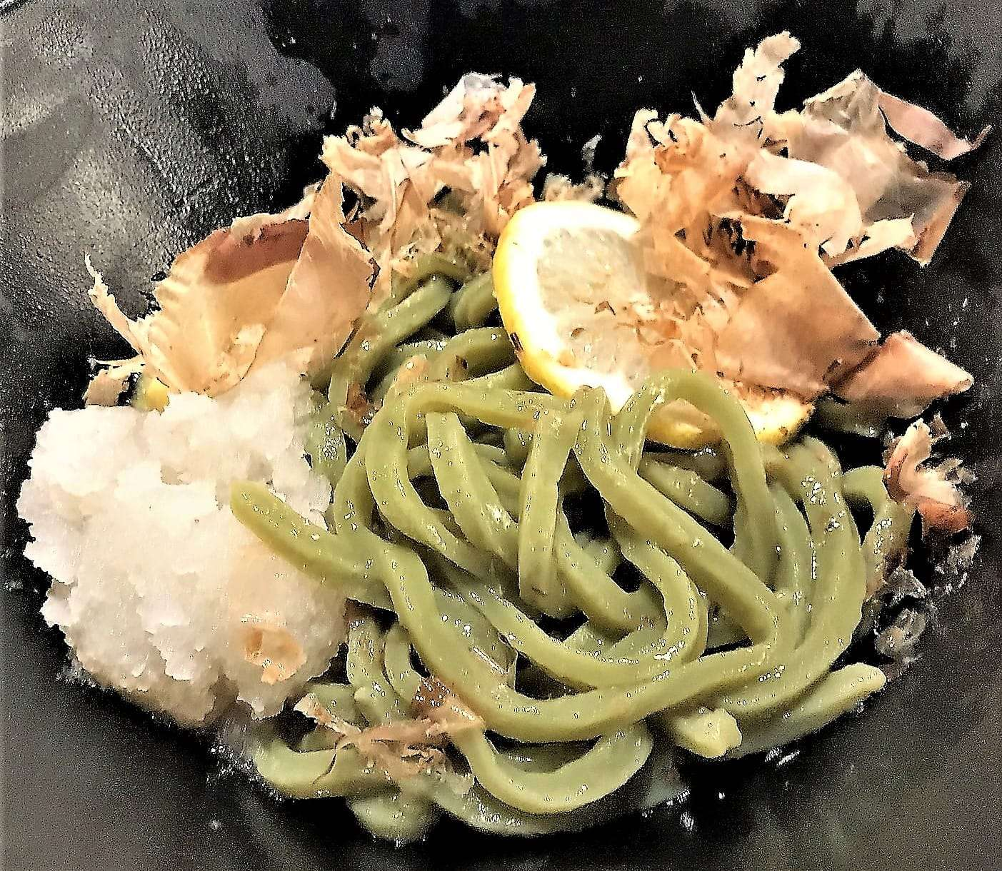Photo of a bowl of udon soup with matcha-colored noodles