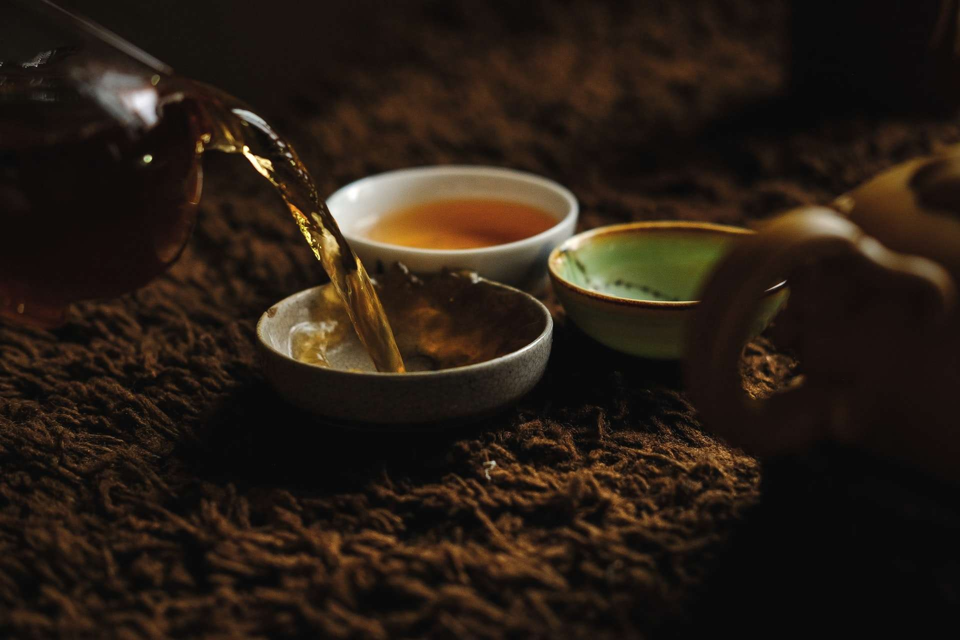 Photo of tea being poured into three differently-colored ceramic tea cups