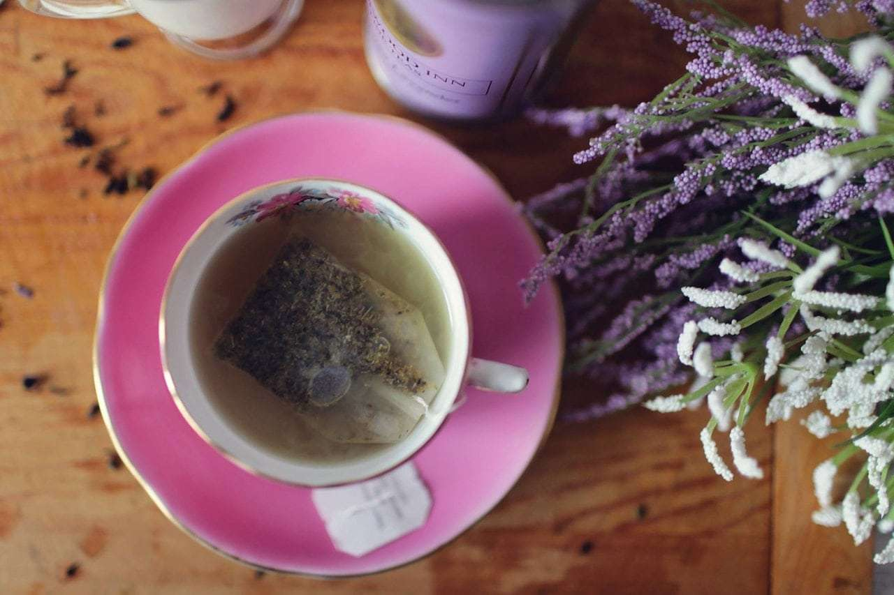 Photo of a cup of tea and saucer with hot water and a tea bag full of lavender; nearby are lavender blooms
