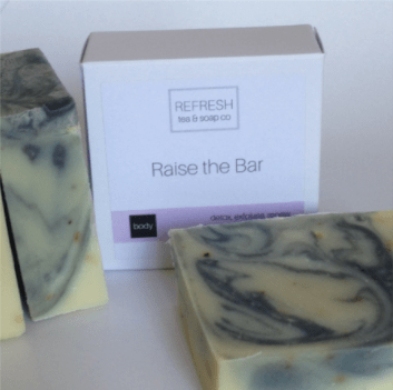 "Photo of a bar of tea soap and its box which has the fragrance name ""Raise the Bar."""
