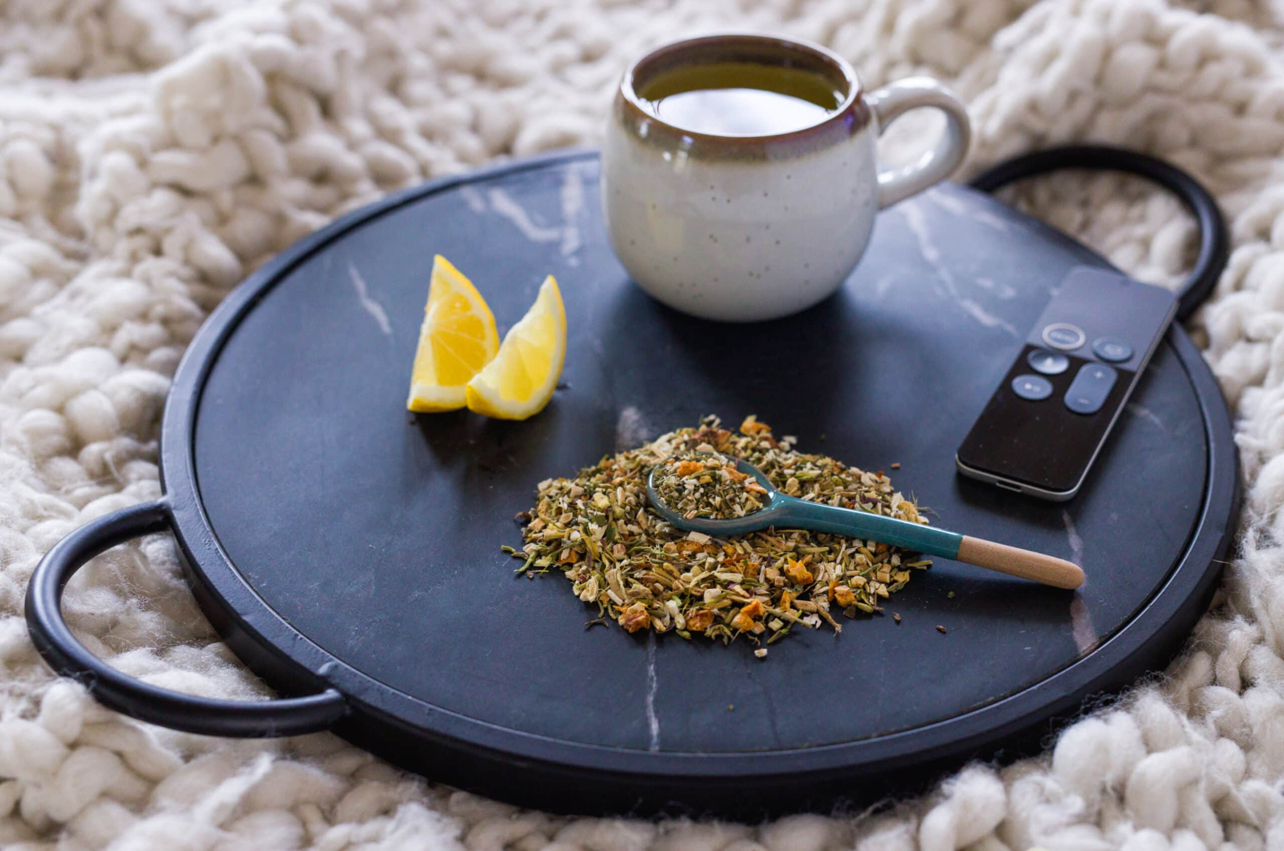 Photo of a tray with a cup of tea, a slice of lemon, a remote, and a pile of loose Flu Fighter tea.
