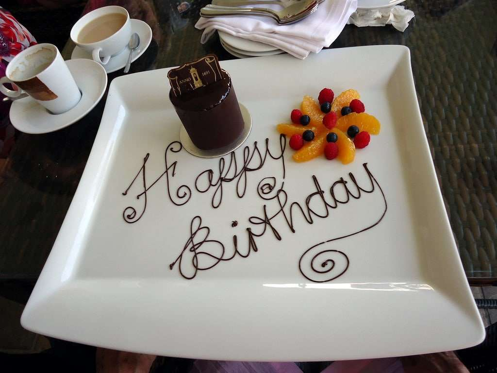 """Photo of a plate with the words """"Happy Birthday"""" written in chocolate, with fruit arranged in the shape of a flower. Next to the plate sits a cup of tea."""