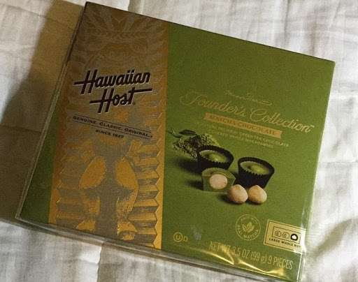 Photo of a package of Hawaiian Host Matcha Green Tea Chocolate Covered Macadamias on a fabric surface.
