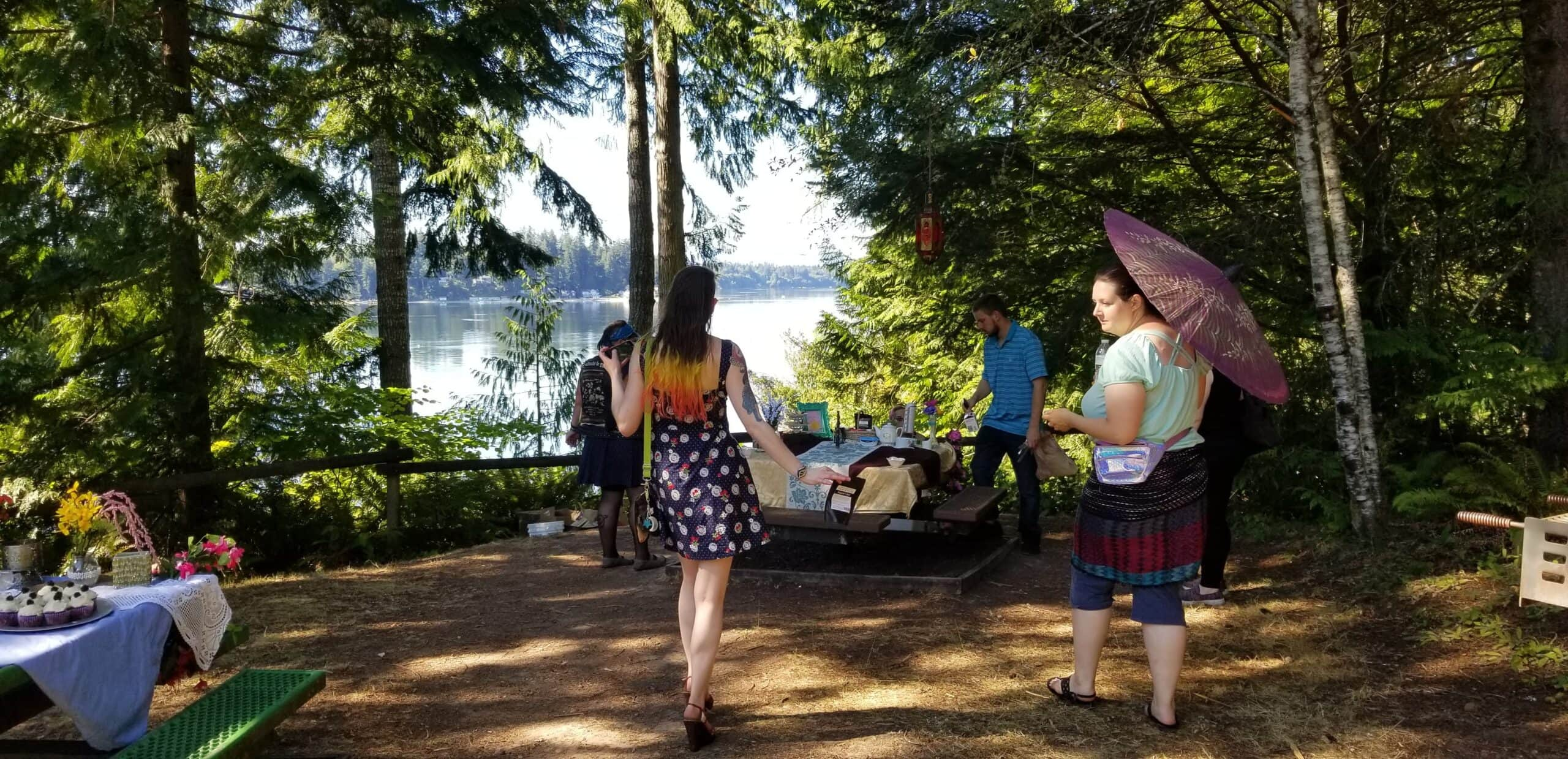A photo of a clearing surrounded by trees, with a bay in the background. There is a decorated table with tea and goodies, and the author's back is to the camera as she walks up to the table.