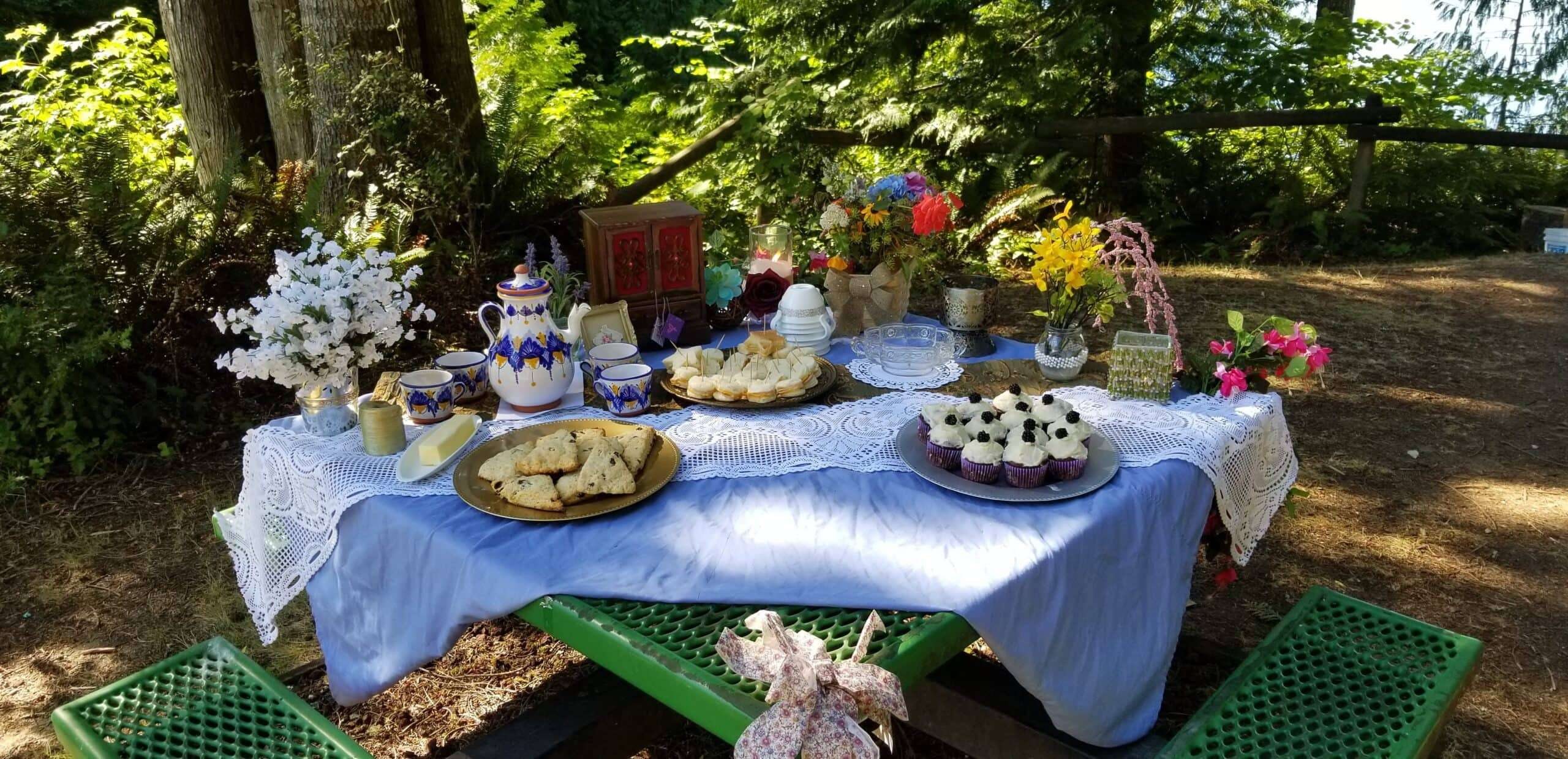 A picture of a table decorated and covered in goodies and flowers.