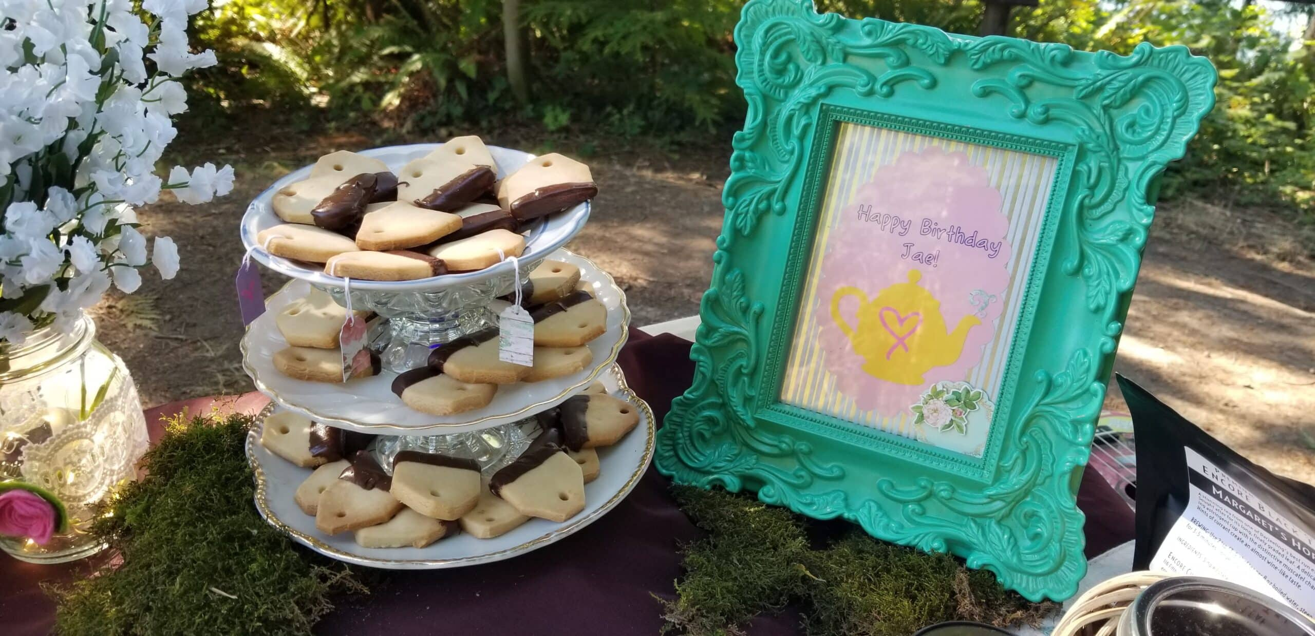 "A photo of a tiered treat stand holding cookies shaped like teabags next to a frame with a cutout of a teapot and the words ""Happy Birthday Jae!"""