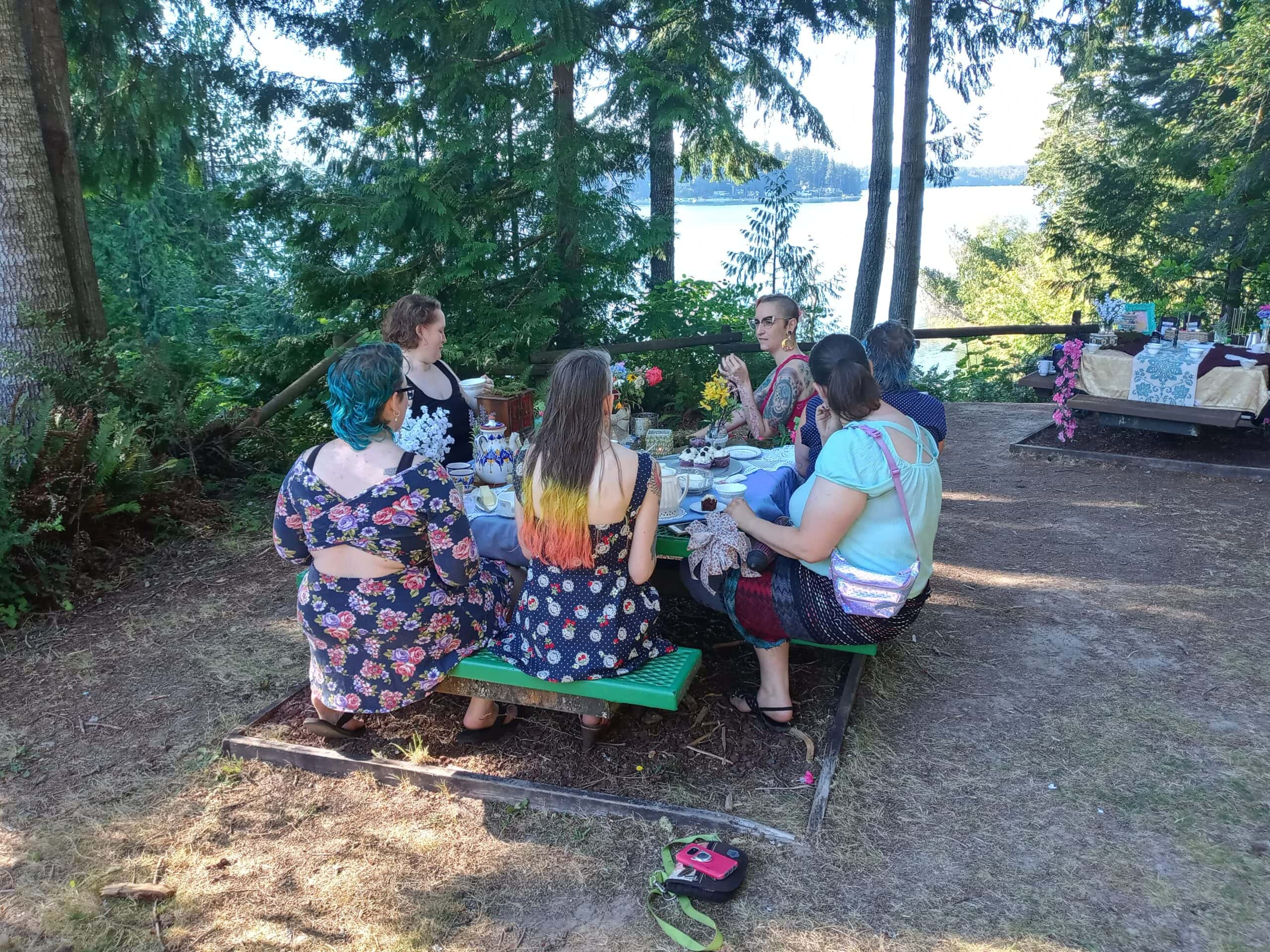 A photo of a small group of people sitting around a picnic table sipping tea.