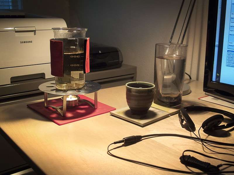 Photo of a desk with a computer, and a cup for tea next to a small glass beaker of water with blooming tea heating over a small candle. Very scientific.