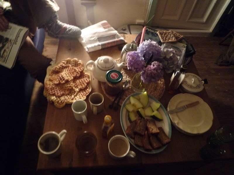 Photo of a table spread with tea and various foods, including waffles, breads, and fruits.