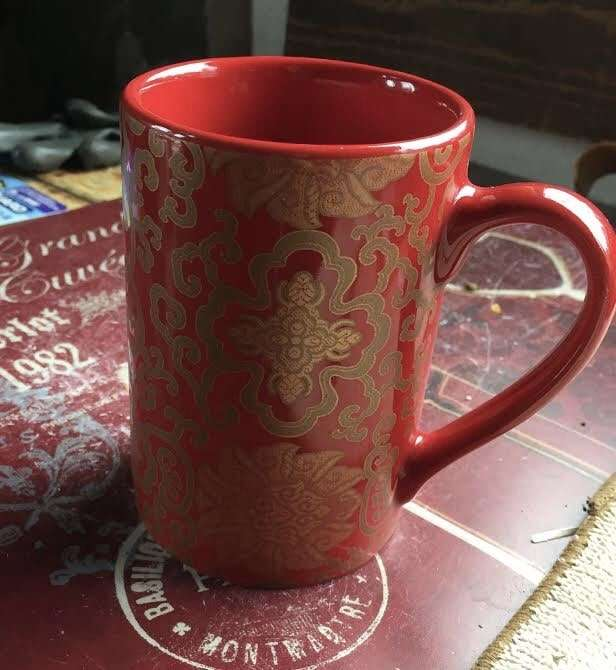 Photo of a mug printed with an ornate filigree pattern.