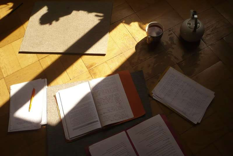 Photo of a wood floor with study materials strewn across it, with a pot and cup of tea nearby.