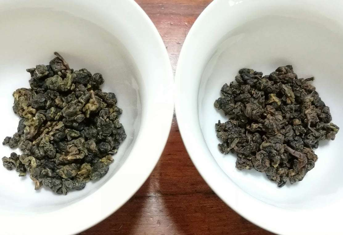 Photo of two gaiwan, each with some dry aged oolong leaves in the bottom.
