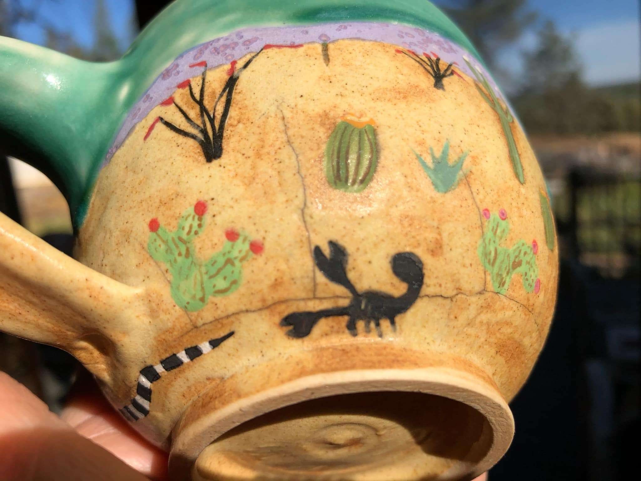 When A Tea Person Moves - A photo of the cup made by Catherine. It has cactus plants and scorpions on it.
