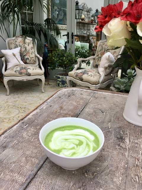 The Essential Guide to Matcha: Japanese Matcha Versus Imposters - A photo of a foamy cup of matcha on a table with a table and chairs in the background