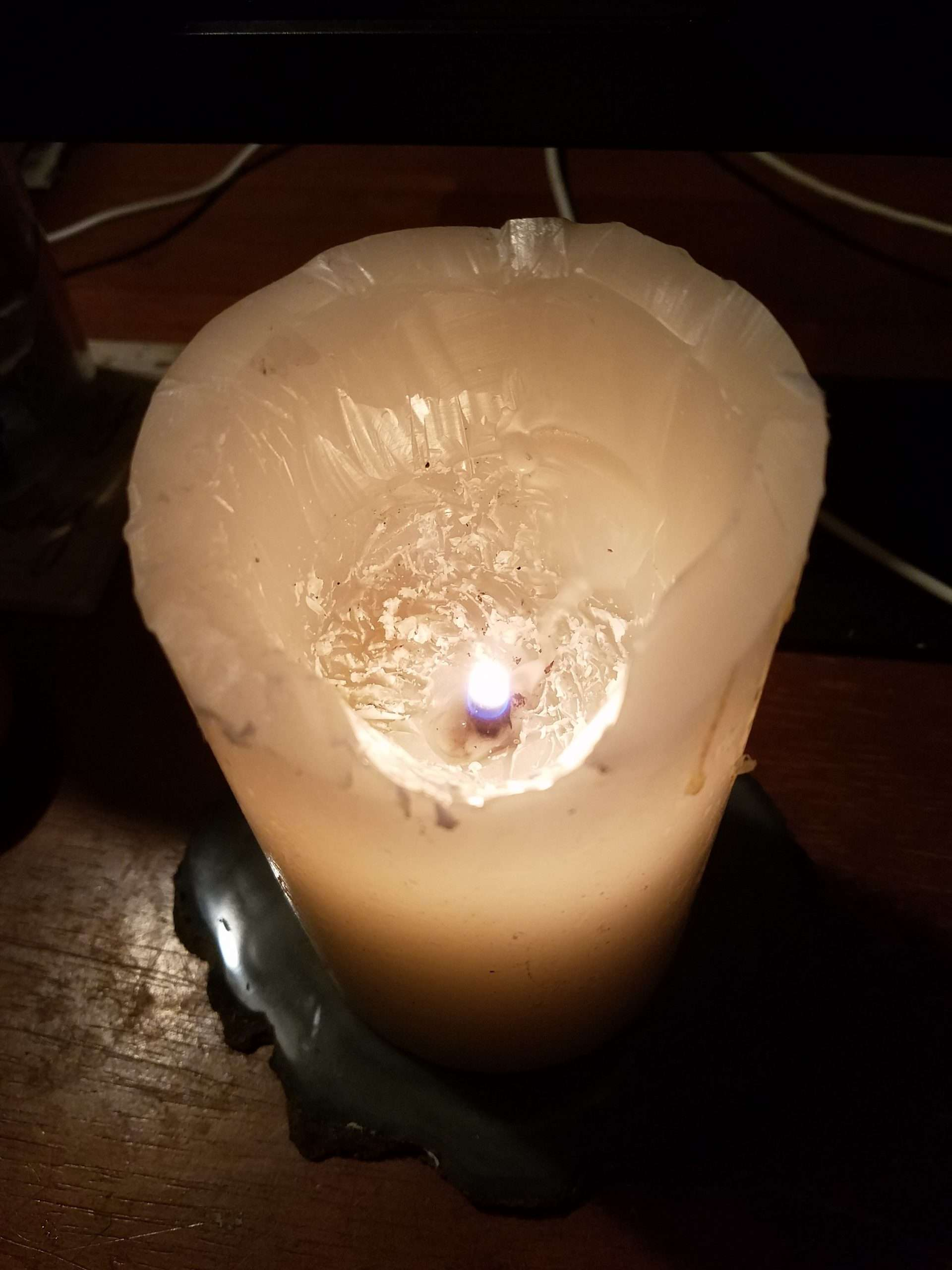 Solstice Night, Tea, and Light - Photo of a just-lit candle, with the wax still jagged