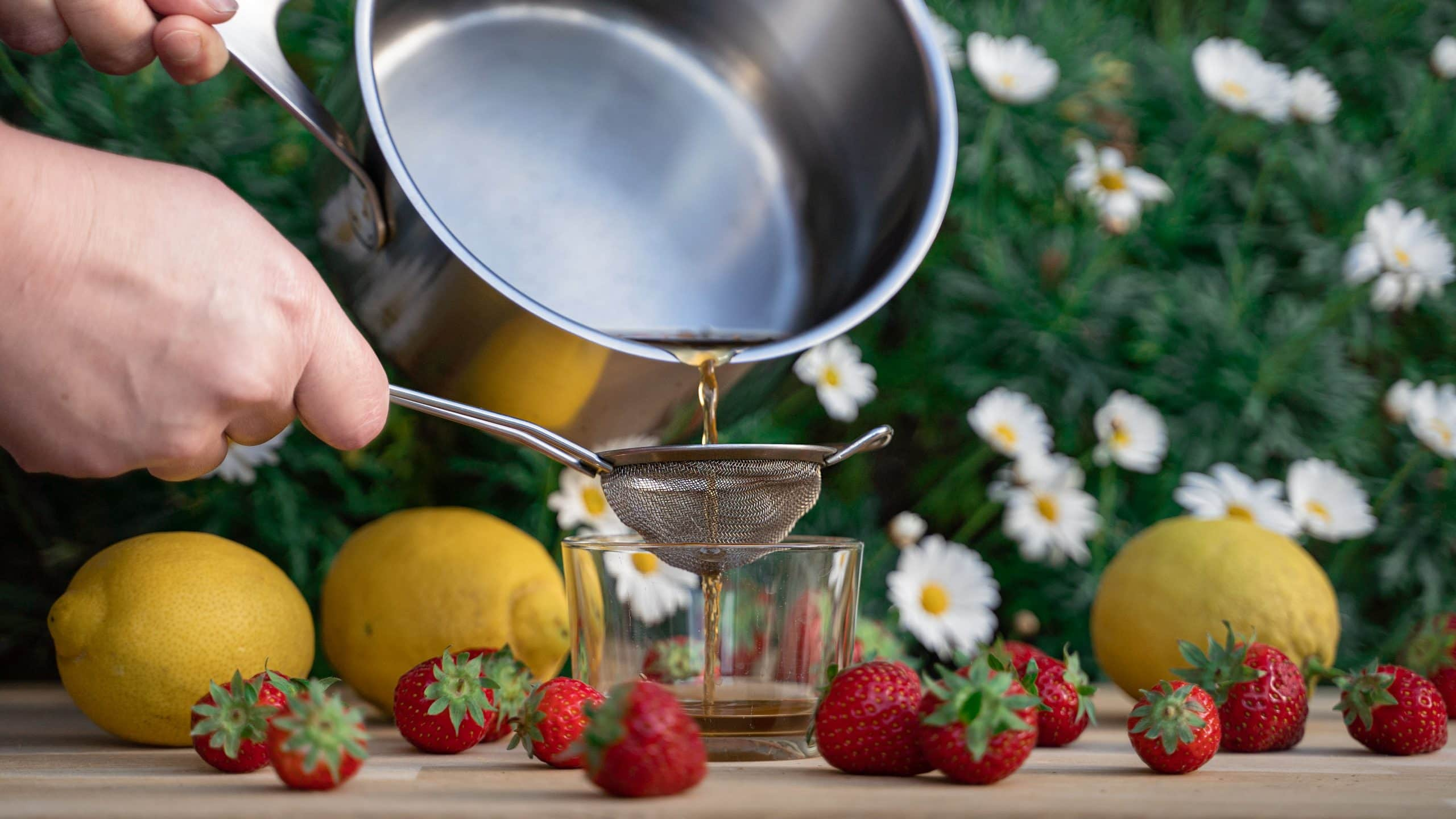 The Best Teas To Pair With Your Barbecue - Photo of straining tea with strawberries and lemons nearby